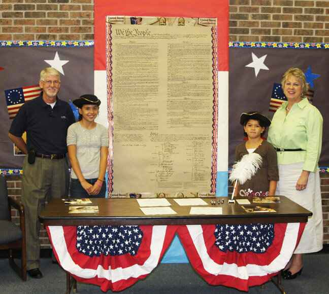 Okmulgee Elementary School celebrated CONSTITUTION DAY Friday. Above, Cate BlueEagle and McKenzie Moen pose beside the s...